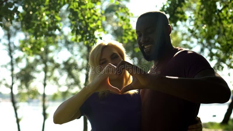 Couples amoureux de métis montrant la forme de coeur avec des mains, mariage interracial photo libre de droits