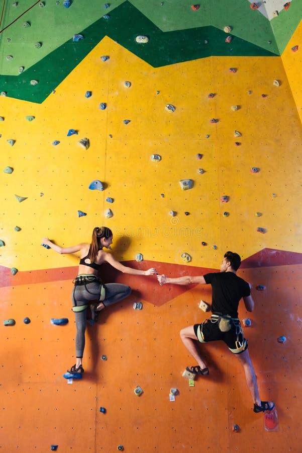 Couples amusés escaladant le mur ensemble photographie stock libre de droits