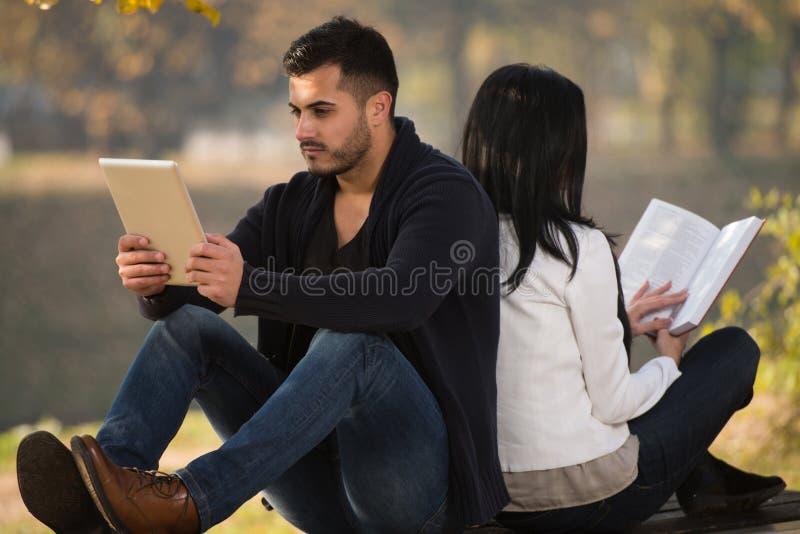 Couples appréciant la Tablette et le livre de Digtial photos libres de droits