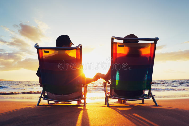 Couples appréciant le coucher du soleil à la plage photos stock