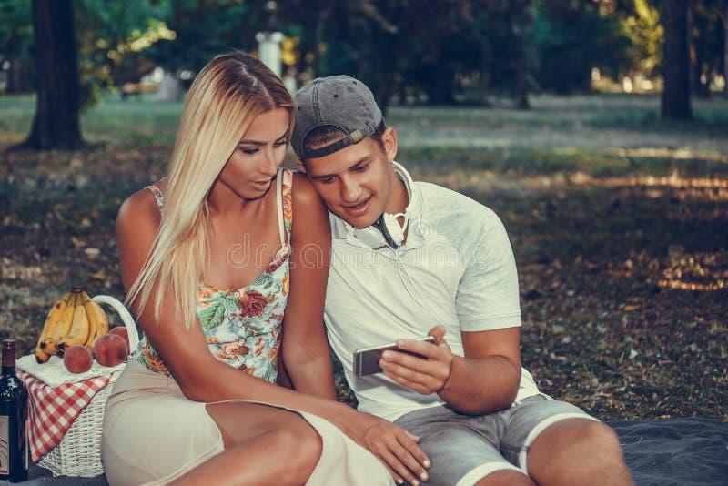 Couples appréciant le jour de pique-nique et écoutant la musique photos stock