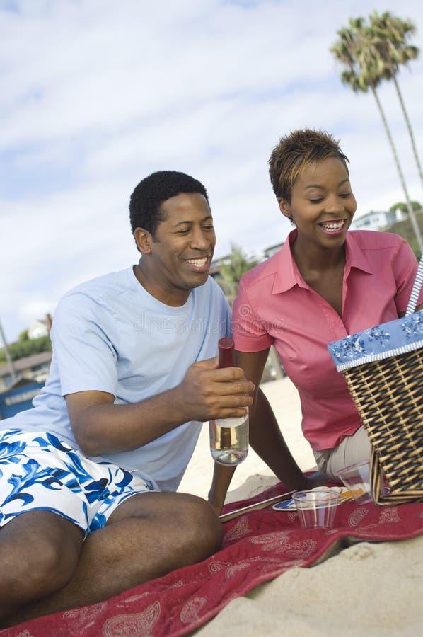 Couples appréciant le pique-nique sur la plage photo stock