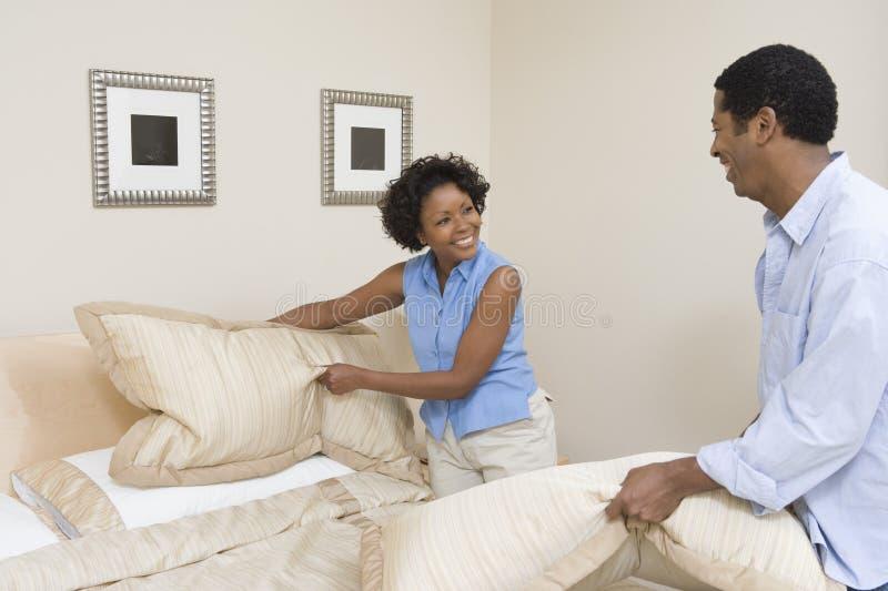 Couples arrangeant des oreillers sur le lit images libres de droits