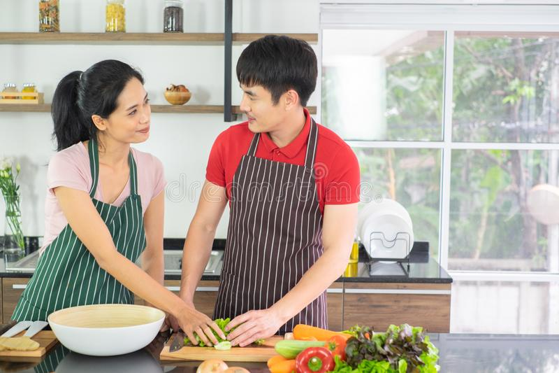 Couples Asian. They both look at each other`s eyes. cooking so fun together in kitchen with full of ingredient on table. royalty free stock image