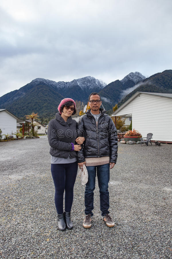 Couples of asian man and woman wearing winter clothes standing. Couples of asian men and women wearing winter clothes standing in front of snow mountain in stock image