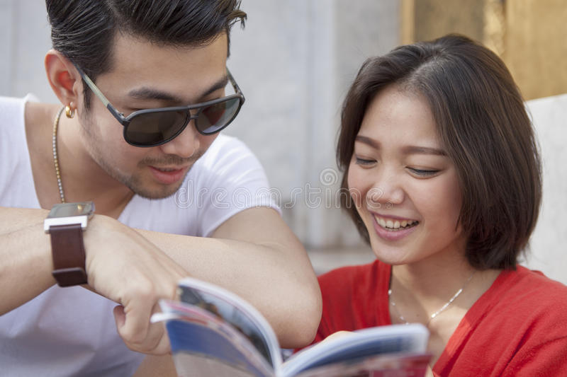 Couples of asian younger traveling man and woman reading a guide. Couples of asian younger traveling men and women reading a guide book with happiness face stock image