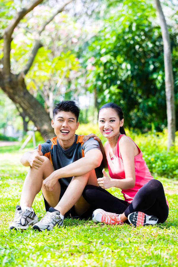 Couples asiatiques ayant la coupure à pendant la formation de sport image stock