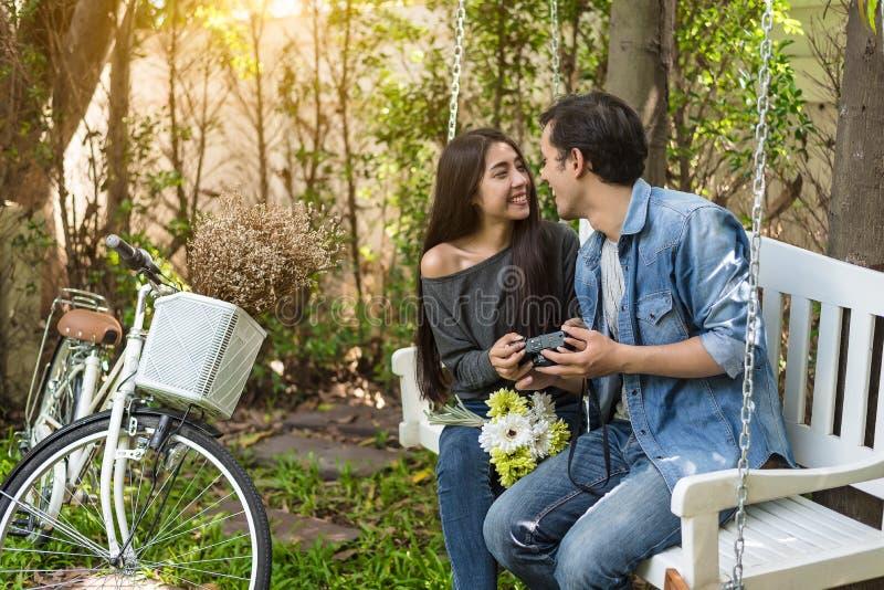 Couples asiatiques ayant le contact visuel en tant que moment romantique au banc dans le parc naturel avec la bicyclette Les gens photos stock
