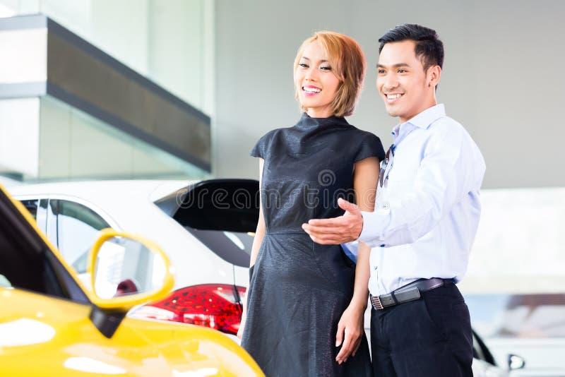 Couples asiatiques choisissant la voiture au concessionnaire photos stock
