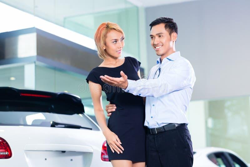 Couples asiatiques choisissant la voiture de luxe de SUV photos libres de droits