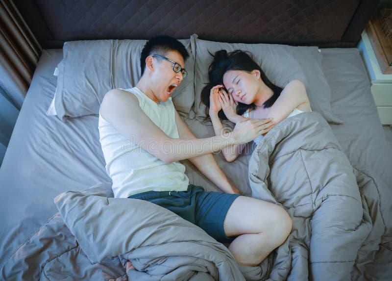 Couples asiatiques fâchés combattant sur le lit la nuit images stock