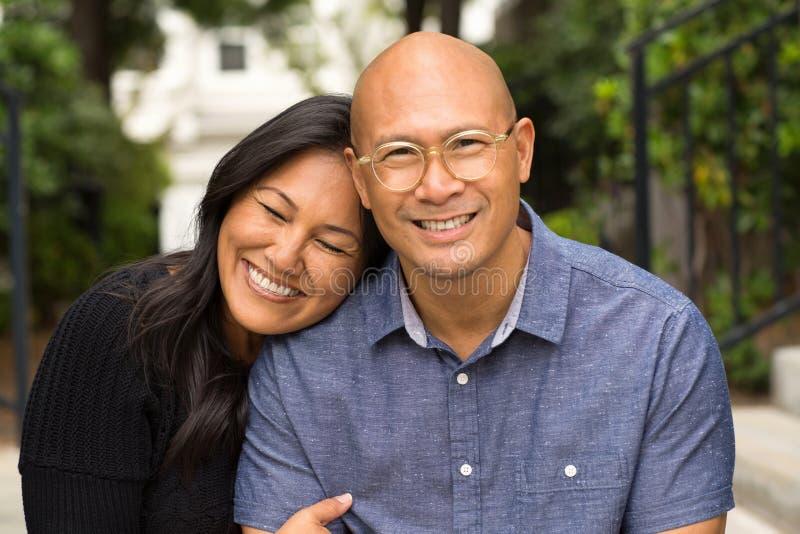 Couples asiatiques heureux souriant et étreignant l'extérieur photographie stock