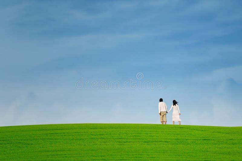 Couples asiatiques marchant sur la colline verte images stock