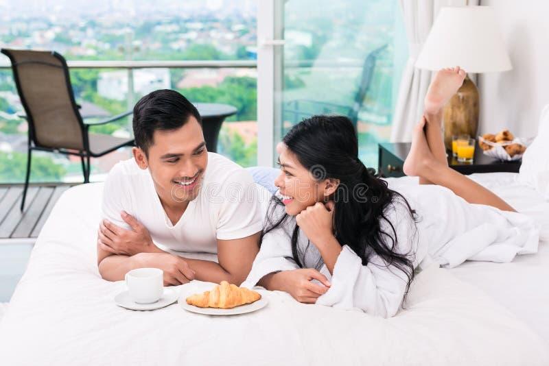 Couples asiatiques prenant le petit déjeuner dans le lit image libre de droits