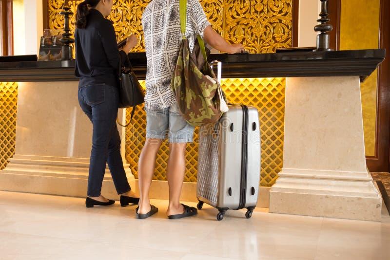 Couples asiatiques signant à la réception d'hôtel photos libres de droits