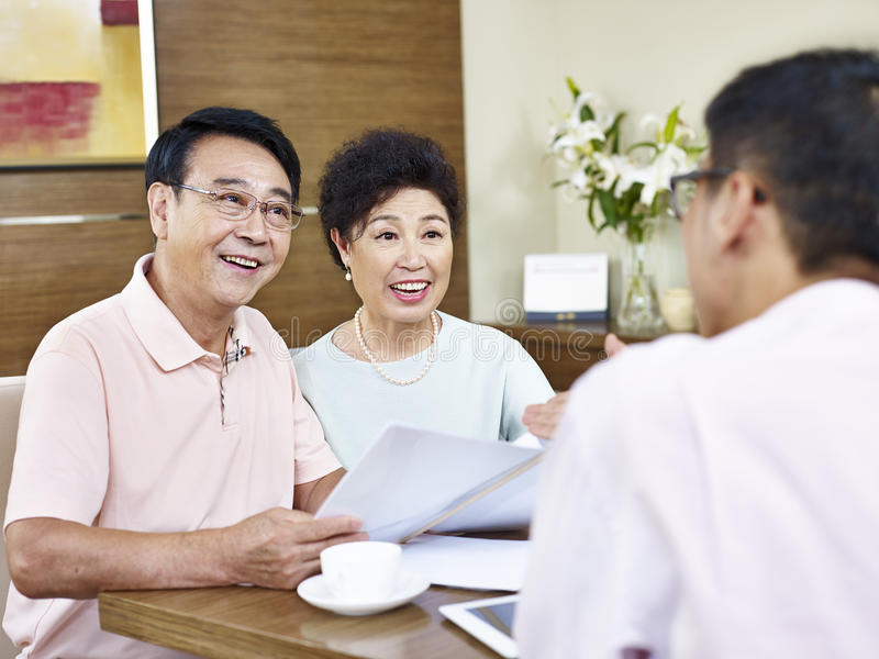 Couples asiatiques supérieurs écoutant un vendeur photographie stock libre de droits