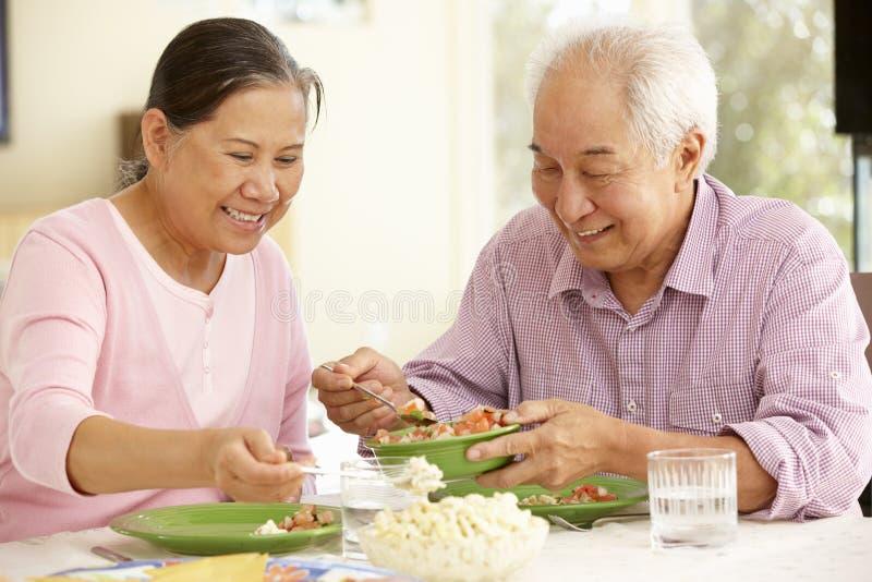 Couples asiatiques supérieurs partageant le repas à la maison image libre de droits