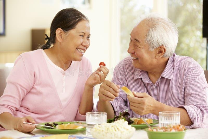 Couples asiatiques supérieurs partageant le repas à la maison image stock