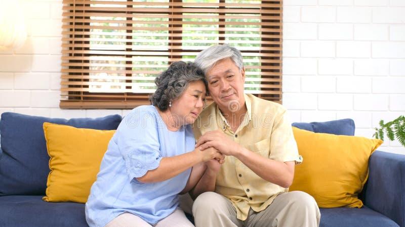 Couples asiatiques supérieurs se soulageant de l'émotion déprimée tout en se reposant sur le salon de sofa à la maison, vieille r photo libre de droits