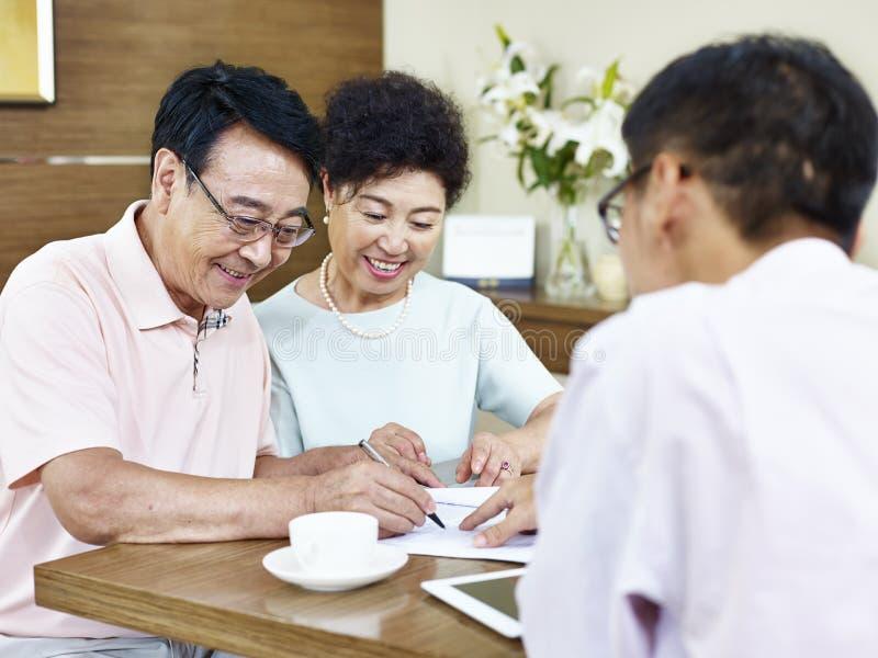 Couples asiatiques supérieurs signant un contrat images libres de droits