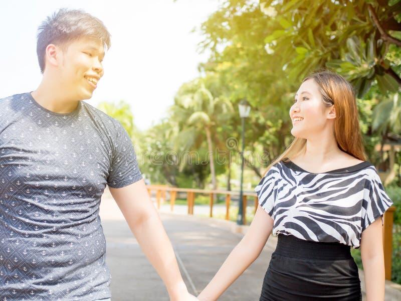 Couples asiatiques tenant des mains et faisant un tour dans la nature verte photo libre de droits