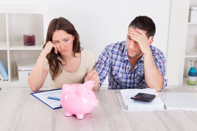 Couples attendant l'argent de la tirelire photo libre de droits
