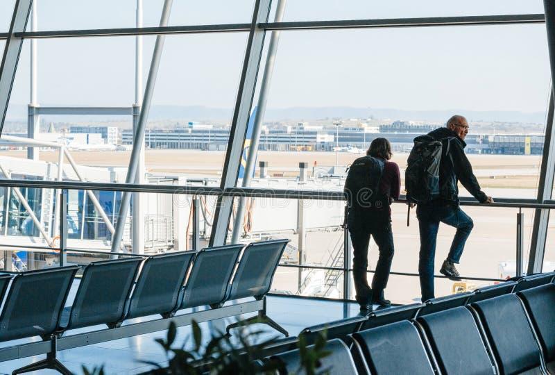 Couples attendant le vol dans le terminal près de grandes fenêtres images libres de droits