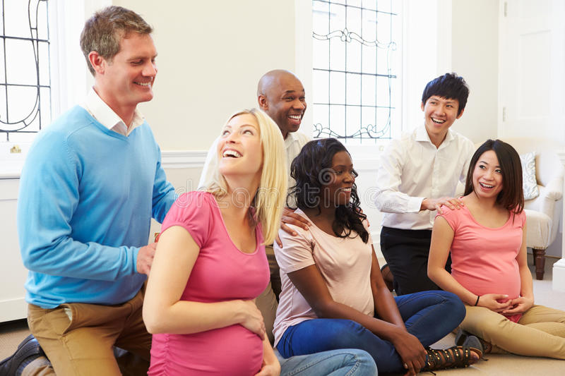 Couples Attending Ante Natal Class Together. Sitting Down With Hands On Shoulders stock photo