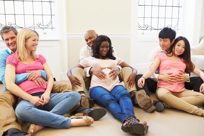 Couples Attending Ante Natal Class Together. Sitting On Floor Feeling Pregnant Belly stock photo