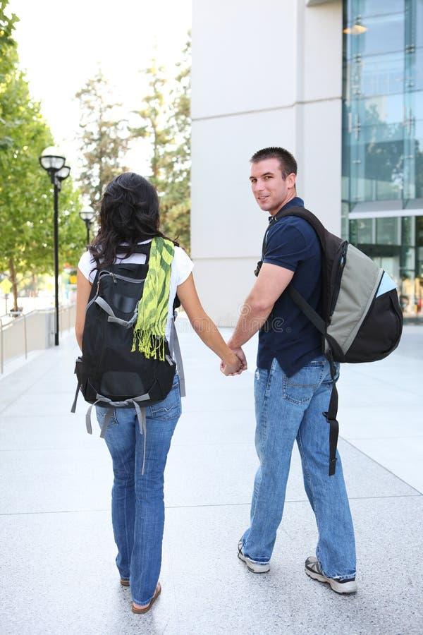 Couples attrayants à la bibliothèque d'école image libre de droits