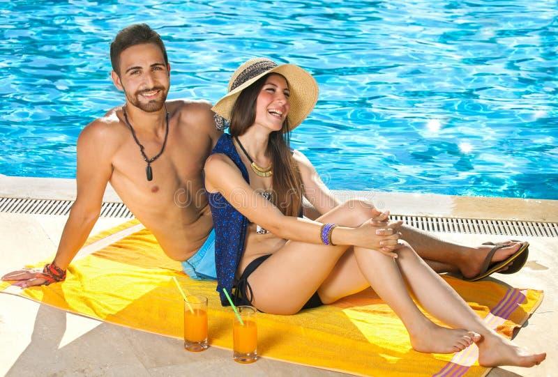 Couples attrayants détendant à côté d'une piscine photographie stock