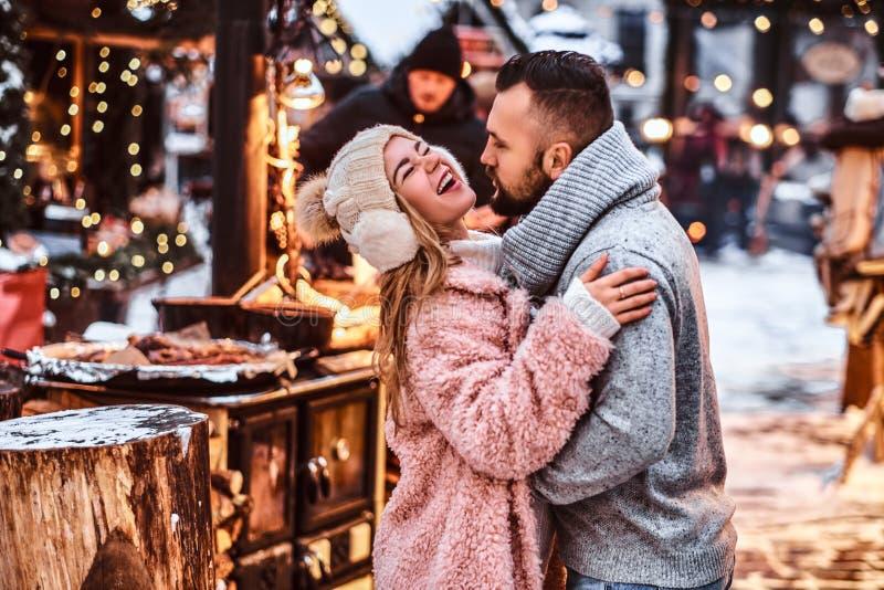 Couples attrayants dans l'amour, appréciant passant le temps ensemble tout en embrassant à la foire d'hiver à un temps de Noël images stock
