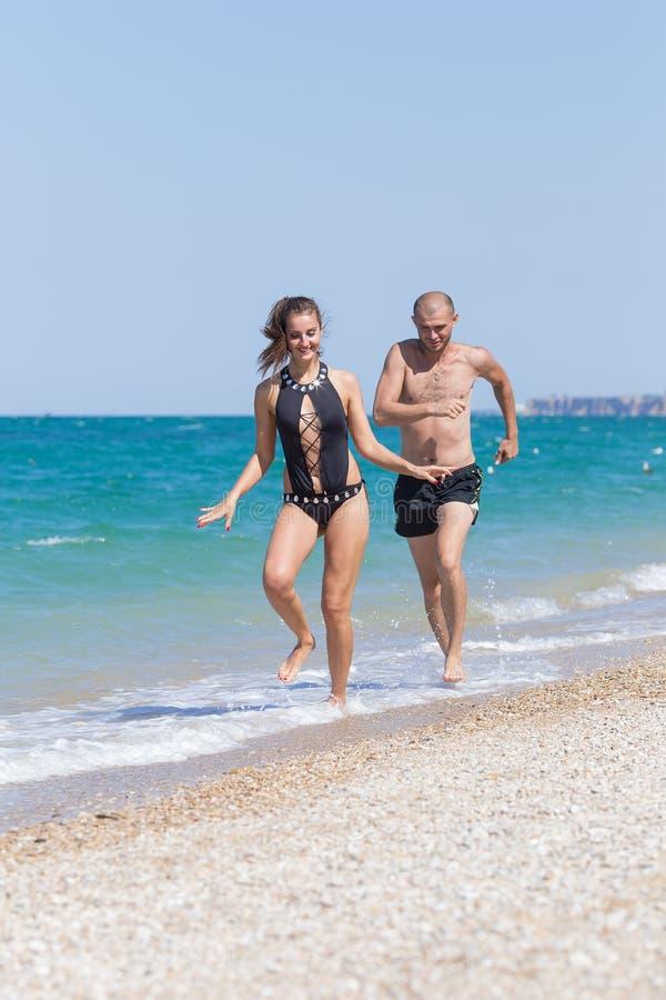 Couples attrayants dans les vêtements de bain fonctionnant le long du bord de la mer images libres de droits