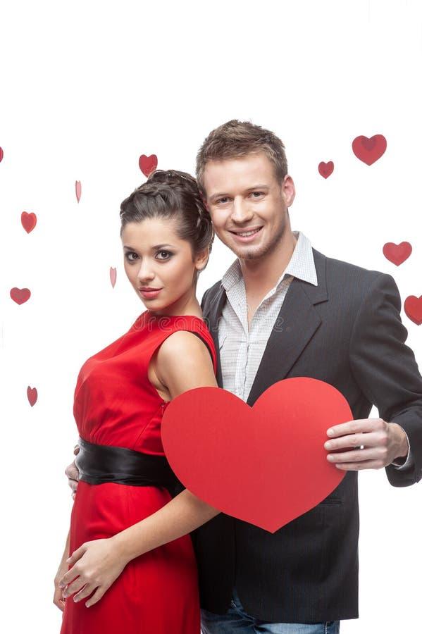 Couples attrayants et bien habillés posant dans le studio photographie stock libre de droits