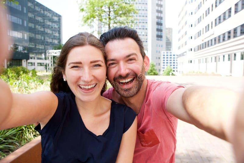 Couples attrayants heureux prenant le selfie dehors dans la ville photos stock
