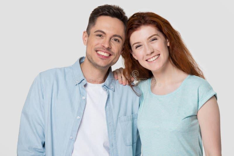 Couples attrayants heureux tirés principaux de portrait de studio sur le fond gris photographie stock libre de droits