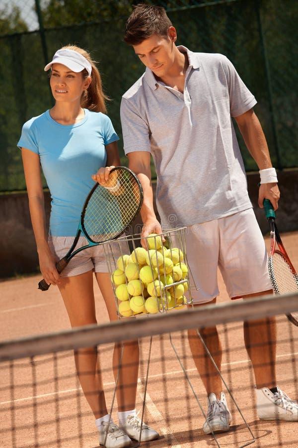 Couples attrayants jouant au tennis photographie stock