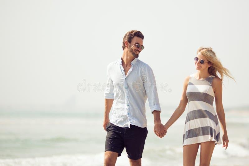 Couples attrayants marchant sur la plage image stock