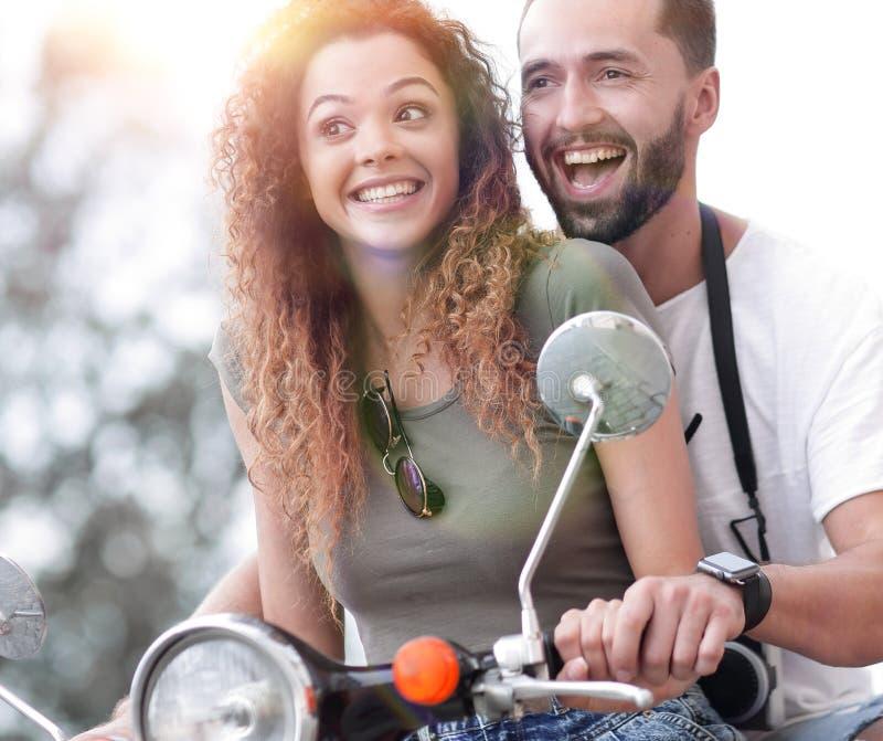 Couples attrayants montant un scooter un jour ensoleillé dans la ville image libre de droits