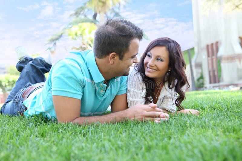 Couples attrayants sur l'herbe photos stock