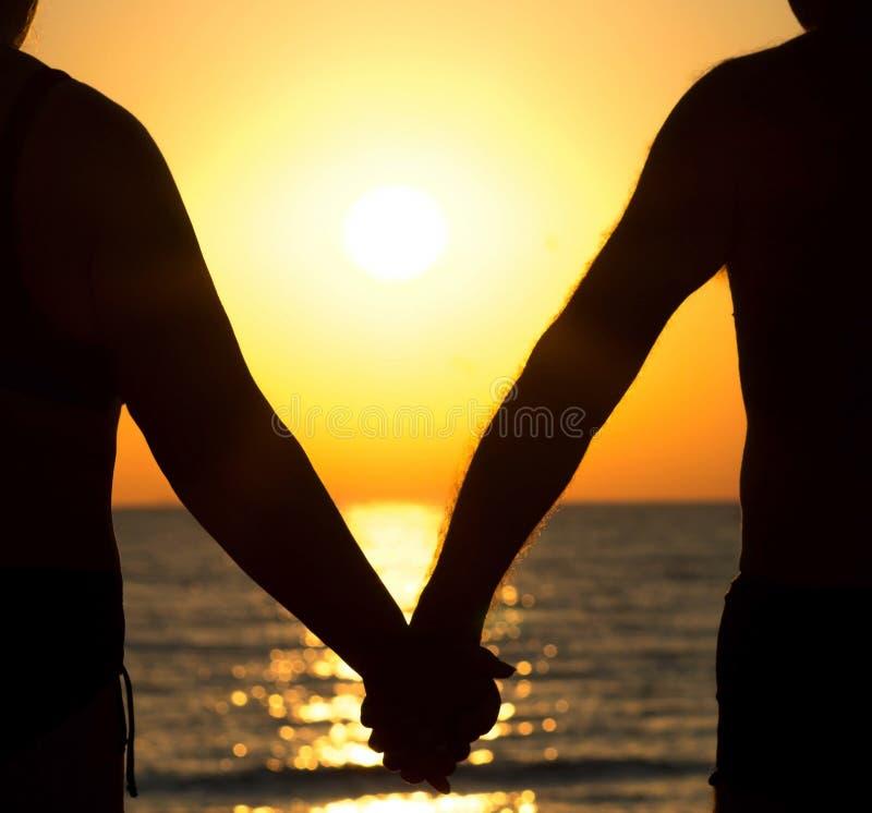 Couples au coucher du soleil tenant des mains photo stock