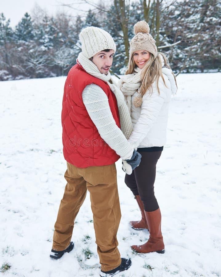 Couples augmentant par la neige en hiver photos stock