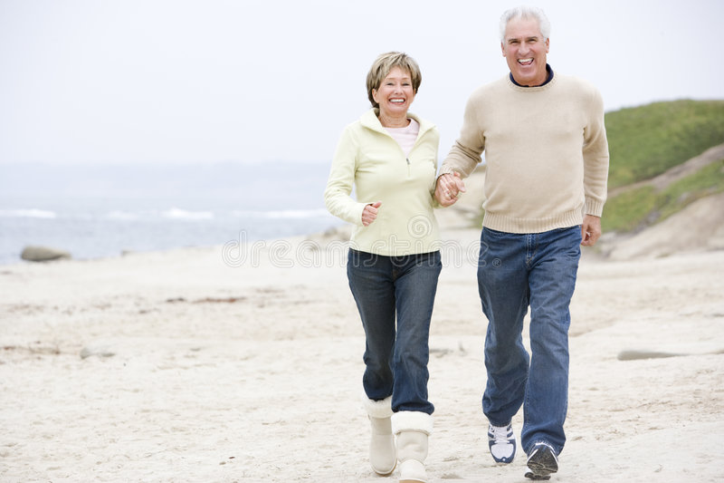 Couples aux mains et au sourire de fixation de plage photographie stock libre de droits