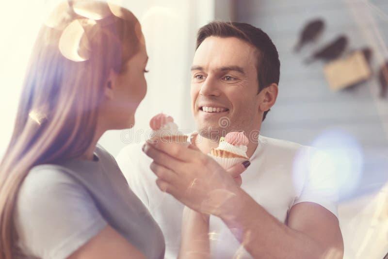 Couples avec du charme heureux goûtant les petits gâteaux images stock