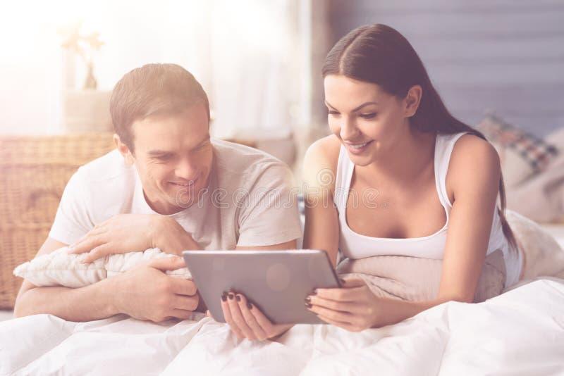 Couples avec plaisir observant quelque chose sur le comprimé photos stock