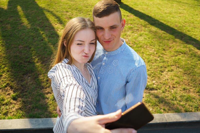 Couples ayant l'amusement à l'extérieur Jeune homme et femme prenant le selfie, m images stock