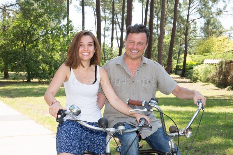 Couples ayant l'amusement en le vélo en vacances images libres de droits