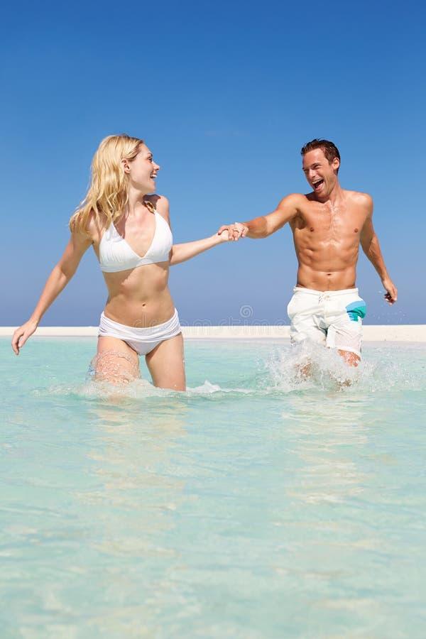 Couples ayant l'amusement en mer des vacances de plage photo libre de droits