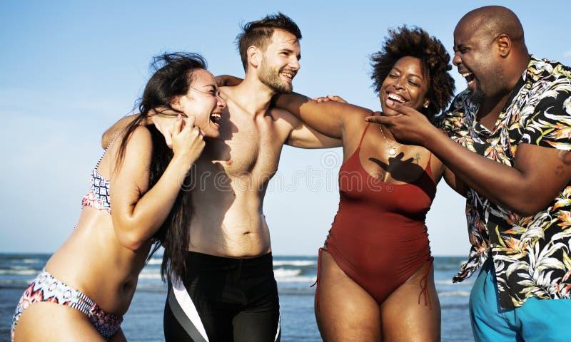 Couples ayant l'amusement ensemble sur la plage images stock