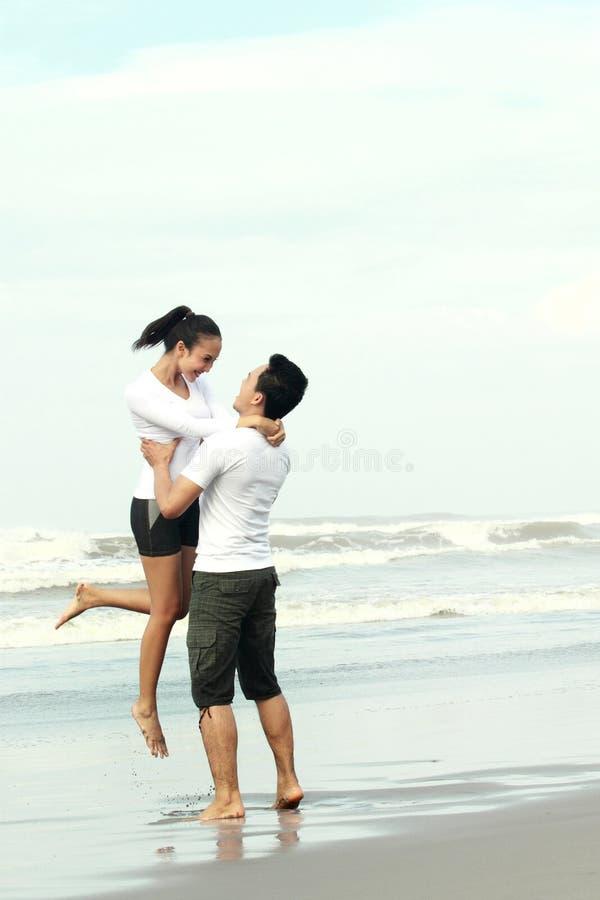 Couples ayant l'amusement sur la plage photo stock
